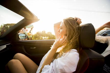 De jonge vrouw gebruikt mobiele telefoon en zit in cabriolet bij de zomerdag Stockfoto
