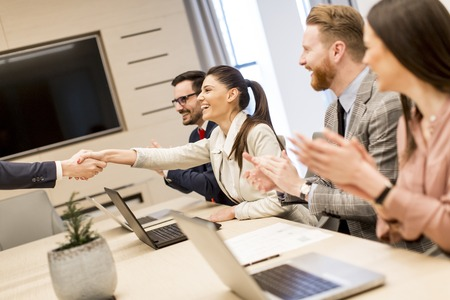 Business people shaking hands finishing up a meeting in modern office Stock Photo