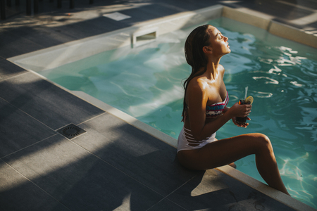 Pretty young woman by the swimming pool with coctail