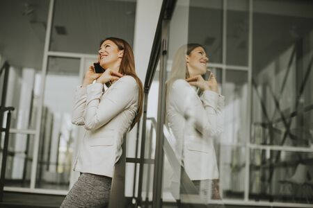 Young businesswoman with mobile phone in front of office building Stock Photo