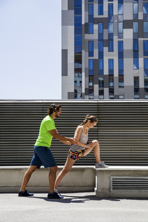 Hansome young couple stretching in the urban environment Stock Photo