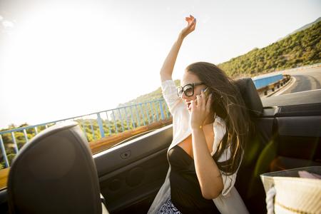 De jonge vrouw gebruikt mobiele telefoon en zit in cabriolet bij de zomerdag Stockfoto - 84055502