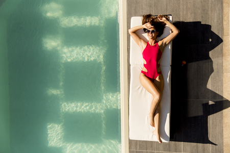 Young woman lying by the pool on sunbed at ot summer day Фото со стока