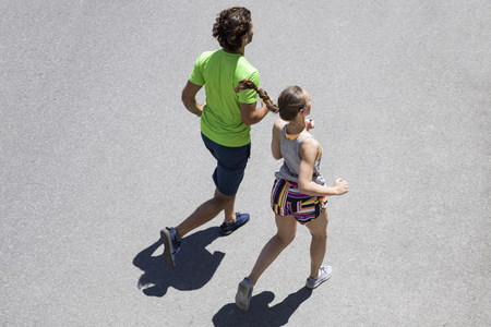 Handsome man and beautiful woman jogging together on street at sunny day