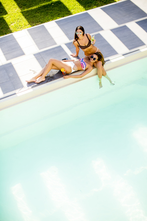 Jonge vrouw drinken cocktail en plezier bij het zwembad op hete zomerdag