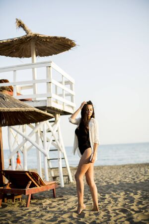 View at young woman posing on the beach by lifeguard observation tower Foto de archivo