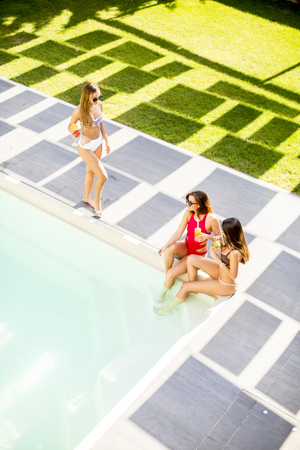 Young woman having fun and drinking coctail by the pool at hot summer day, View from above