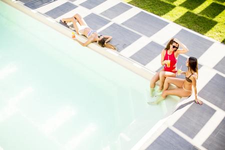Jonge vrouw die pret hebben en coctail drinken door de pool bij hete de zomerdag, Mening van hierboven