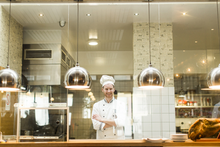 Portrait of smiling young chef in the kitchen