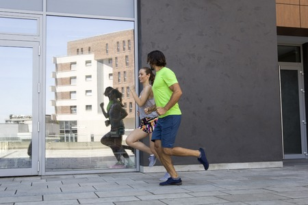 Young couple running in the urban environment on a sunny summer day