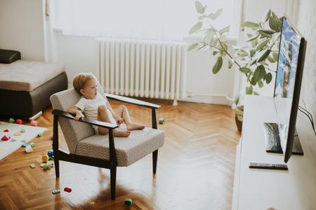 안락의 자에 앉아서 방에서 텔레비전을 보는 어린 소년