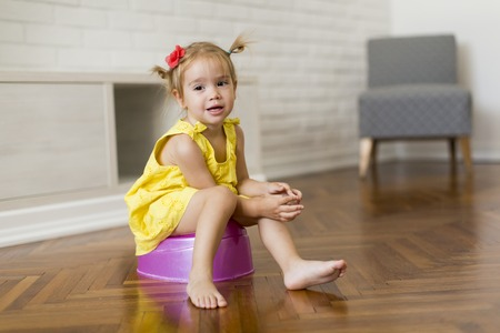 Little girl on the potty in the room