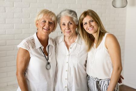 Portrait d'une femme souriante, grand-mère et petite-fille à la maison