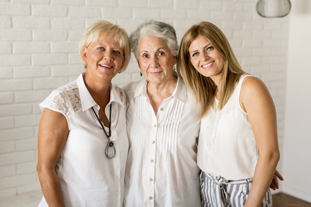 Portrait of a smiling woman , grandmother and granddaughter  at home