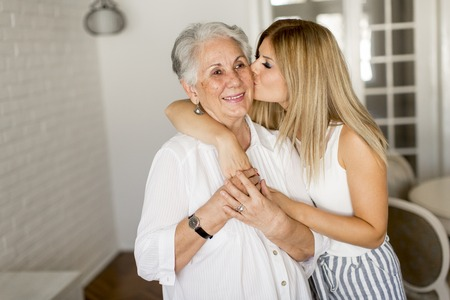 Grandmother kissing granddaughter in the room Stock Photo