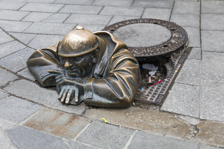 Standbeeldmens aan het werk in Bratislava, Slowakije. Dit bronzen beeld van rioolwerker is in 1997 door Viktor Hulik gemaakt.