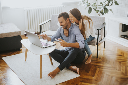 Cheerful couple searching internet on laptop in living room at home Archivio Fotografico