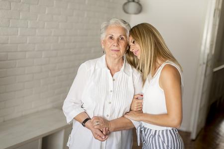 Granddaughter hugging grandmother in the room