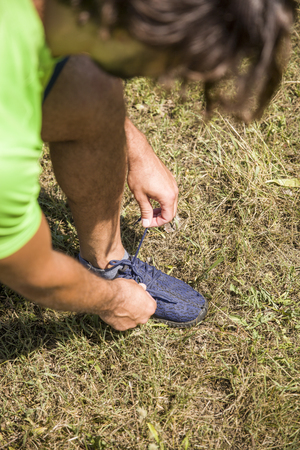 Man doing shoelace tying during exercise in the park