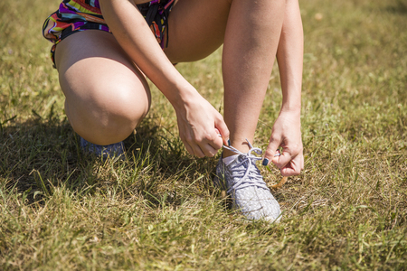 Woman doing shoelace tying during exercise in the park