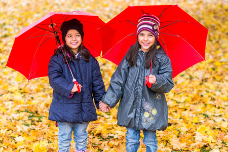 Portrait of happy little girls laughing with  umbrellas in the rain