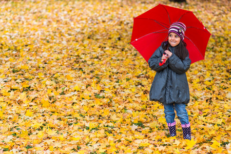Portrait of happy little girl laughing with  umbrella in the rain