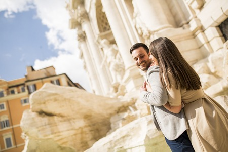 Tourist couple on travel by Trevi Fountain in Rome, Italy.