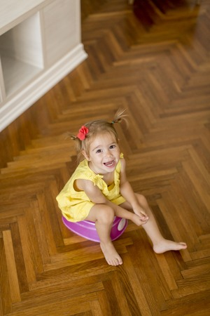 Little girl on potty  in the room at home Stock Photo
