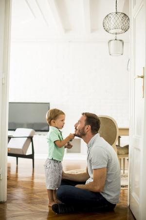 床にホームで演奏彼の息子と父 写真素材