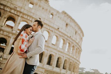 Loving couple visiting Italian famous landmarks Colosseum in Rome, Italy