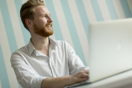 Portrait of young redhair man working on laptop in room by the blue striped wall
