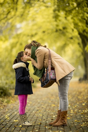 Mother kissing little daughter in the park