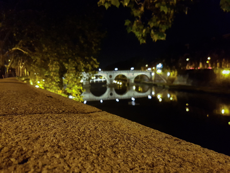 Bridge over the Tiber river in Rome, Italy by night