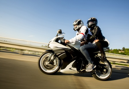 Young man and a woman on a motorcycle by day Stockfoto