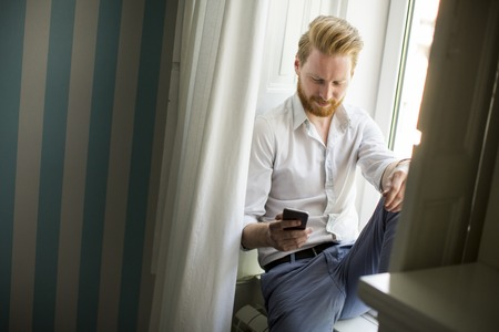 Man with beard and red hairs using smartphone  for reply to messages and sitting on window