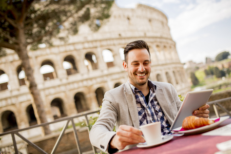 Young man sitting and having a cup of coffee in Rome, Italy Banco de Imagens