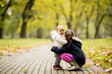 秋の公園で 2 つの小さな女の子の姉妹