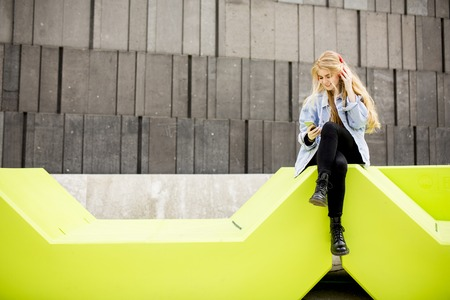 Young woman sitting in the city and use a mobile phone. Urban concept.
