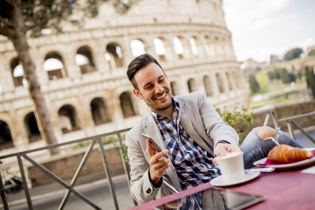 Young man sitting and having a cup of coffee in Rome with Colosseum in background, Italy