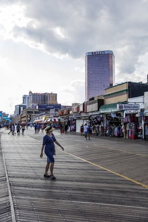 Unidentified people on boardwalk in Atlantic City, USA. City is established in the 1800s as a health resort and today is known for its casinos, beaches and  Boardwalk.