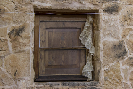 Old wooden window on stone house