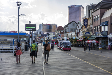 ATLANTIC CITY, USA - AUGUST 25, 2017: Unidentified people on boardwalk in Atlantic City, USA. City is established in the 1800s as a health resort and today is known for its casinos, beaches and  Boardwalk. Editorial