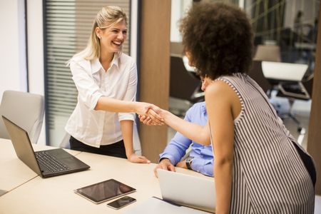 Welcoming business woman giving a handshake and smiling in moden office