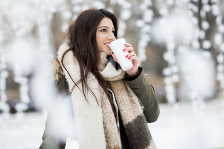 Pretty young woman drinking hot tea on a cold winter day 版權商用圖片