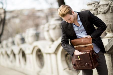 外で待っているビジネスマンは、彼のビジネスケースで何かを探しています