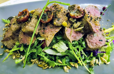 Close up view at beefsteak with green salad Stock Photo