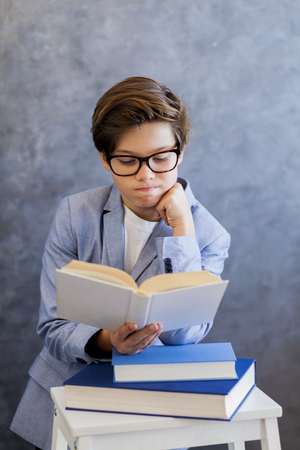 Portrait of cute teenage boy with glasses reading book Stock Photo