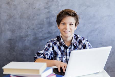 가정에서 랩톱에서 인터넷 서핑을하는 귀여운 십 대 소년 스톡 콘텐츠