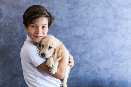 Portrait of teen boy with golden retriever by the wall