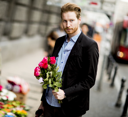 Man standing with a bouquet of roses on the street
